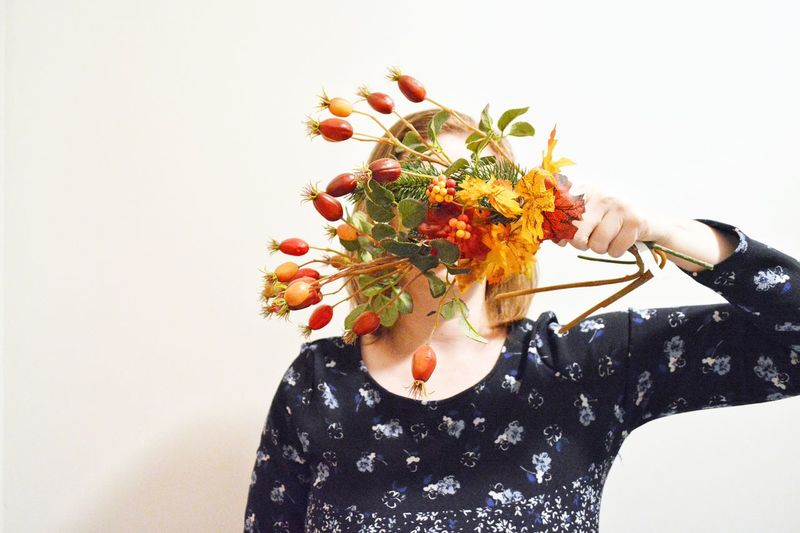 Close-Up Of Woman Holding Rose Hips And Flowers On Face Against White Background