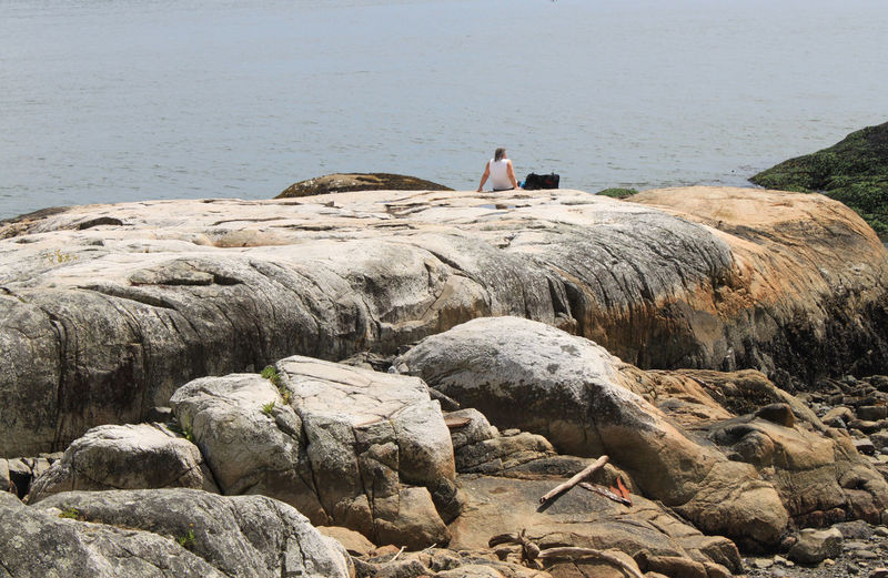 a man sitting on a giant rock near to Vancouver, Canada Allein Calmness Cliff Coast Erholung Felsen Freiheit Idyllic Lifestyles Man Nature Non Urban Scene Outdoors Rock Rock Formation Ruhe Shore The KIOMI Collection Tranquil Scene Tranquility Travel Vacations Water