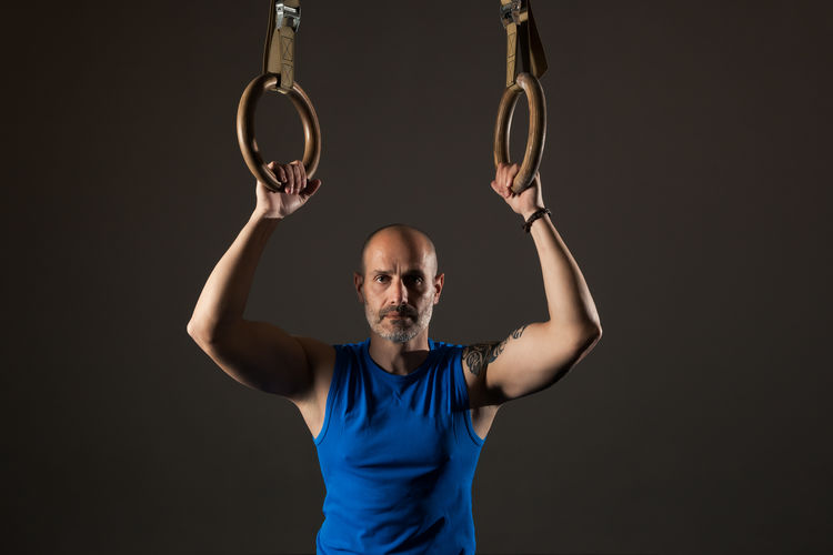 Portrait of man with arms raised against black background