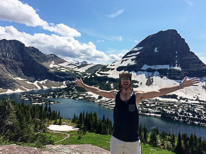 Excited man standing with arms outstretched against bearhat mountain at glacier national park