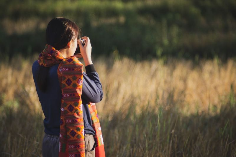 Rear view of woman photographing while standing on field