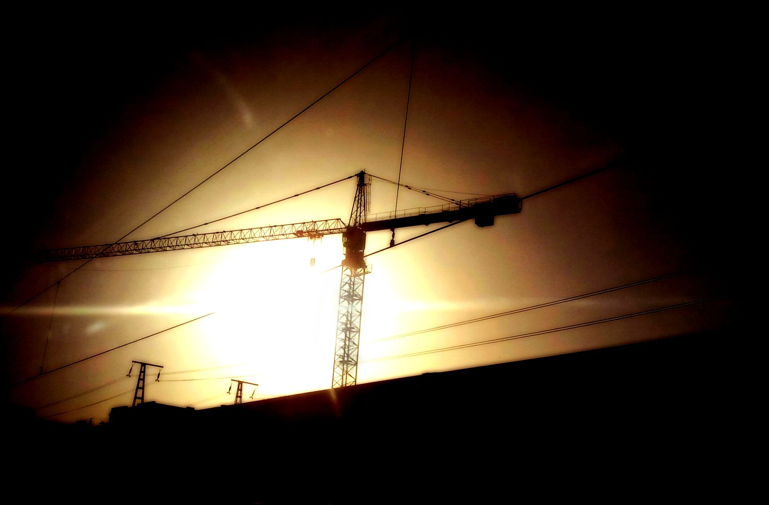 silhouette, sunset, low angle view, electricity, sky, power line, electricity pylon, sun, fuel and power generation, power supply, connection, dark, technology, built structure, cable, dusk, sunlight, no people, orange color, outdoors