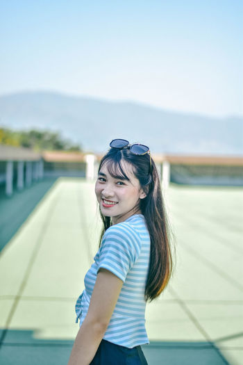 Portrait of smiling young woman standing at building terrace against sky