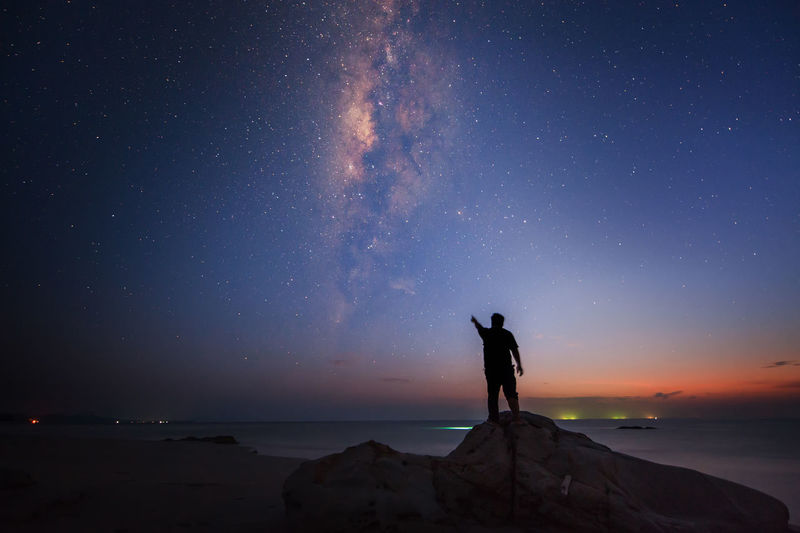 Silhouette of man standing and pointing towards sky at night