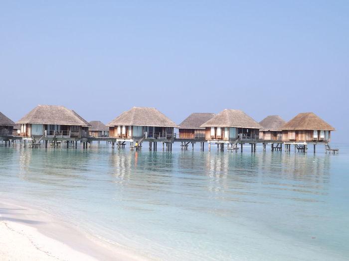 Stilt houses by sea against clear sky