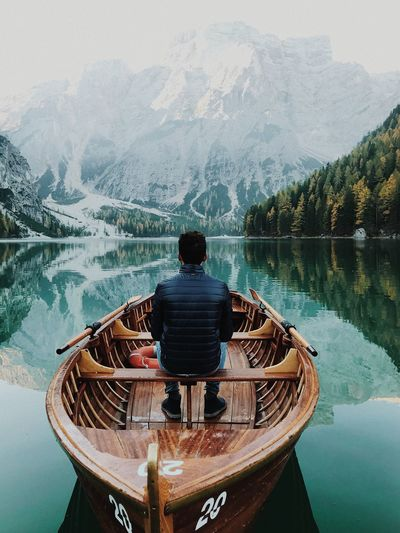 Rear view of young man sitting on boat in lake against mountains
