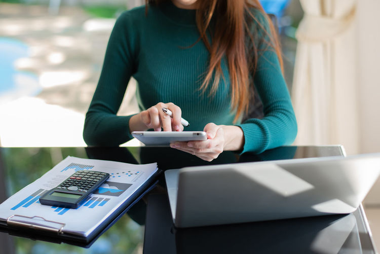Woman using mobile phone while sitting on table