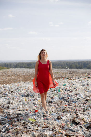 Portrait of young woman walking on garbage