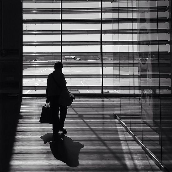 Rear view of silhouette man walking at airport