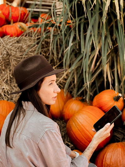 High angle view of woman with orange pumpkins