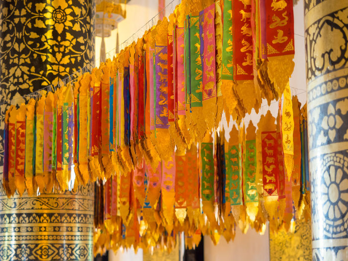 Colorful flags hanging in Chiang Mai temple Wat Chiang Man, Thailand Chiang Mai Golden Thailand Travel Wat Chiang Man Art And Craft Belief Buddhism Decoration Flag Hanging In A Row Indoors  Large Group Of Objects Market Multi Colored No People Place Of Worship Religion Retail  Script Spirituality Temple