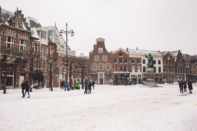 Buildings in city against clear sky during winter