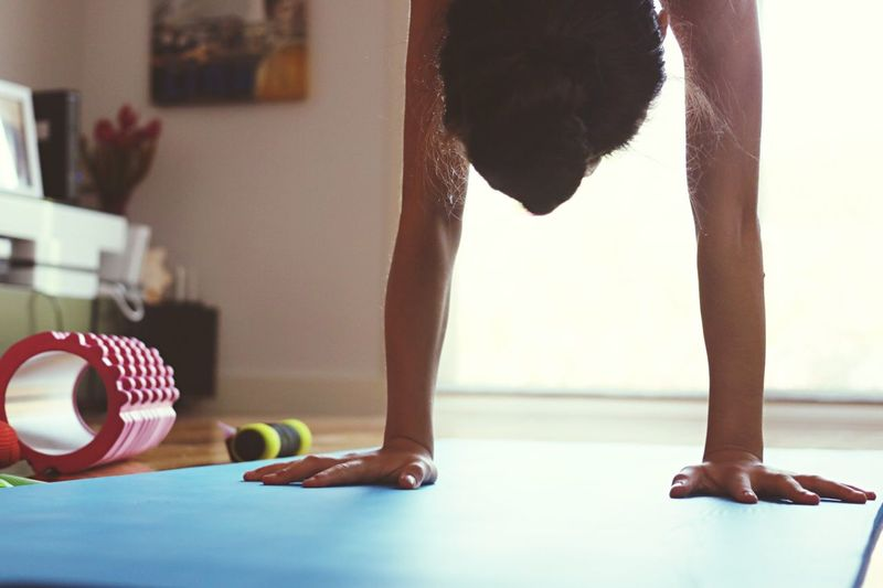 Woman Practicing Handstand On Exercise Mat
