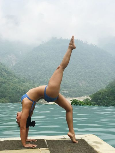 Water Lifestyles One Person Leisure Activity Real People Mountain Nature Full Length Beauty In Nature Day Women Healthy Lifestyle Wellbeing Scenics - Nature Sport Swimming Pool Tranquility Yoga Outdoors