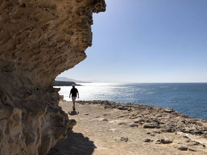 Man standing on rock by sea against sky