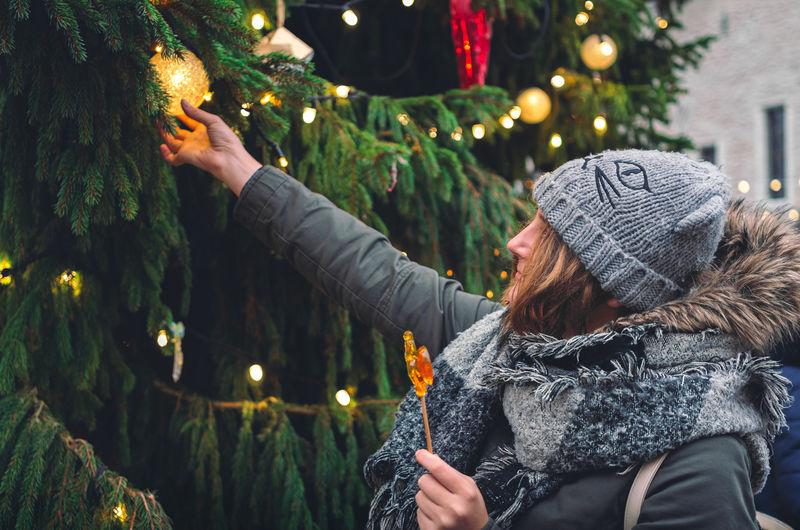 Side view of woman with illuminated christmas tree during winter