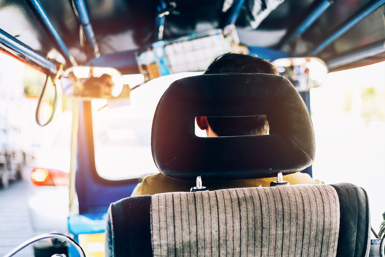 Rear view of man driving rickshaw in city