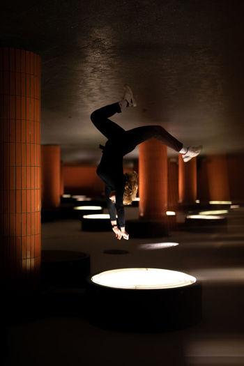 Woman flyibg in illuminated room backwards against white light