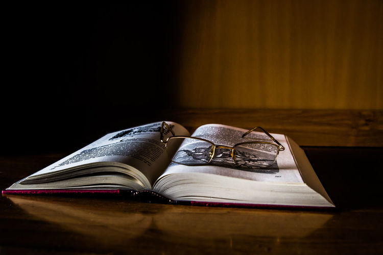 Close-up of eyeglasses over open book on table