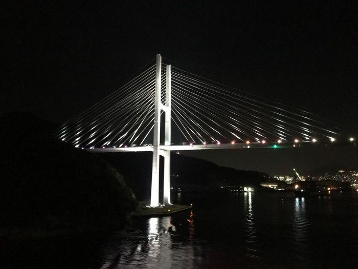 Illuminated suspension bridge over river against sky at night
