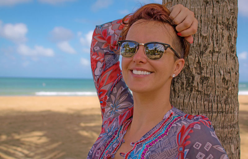 Portrait Of Smiling Young Woman Standing At Beach Against Sky