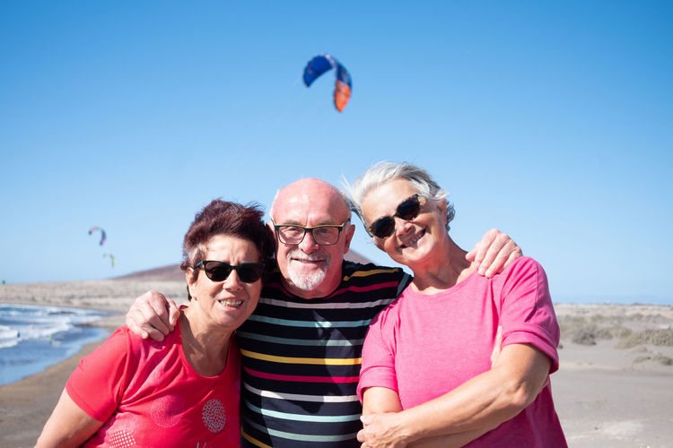 Portrait of happy friends standing at beach against clear sky