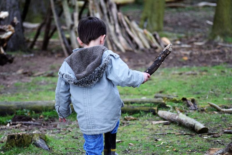 Rear view of boy with wood on field