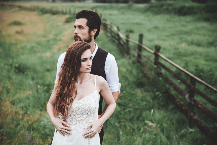 Young couple in love. There are two people in the photo. The man gently hugs the girl from behind. Wedding photo. She is dressed in a white dress, he wears a classic white shirt and vest. He has a beard on his face, she has chic long hair. They are happy. Real emotions. In the background a meadow with green grass and a rough wooden fence. Natural landscape. Couple Fashion Groom Love Nature Relationship Wedding Adult Beautiful Woman Beauty Bride Couple - Relationship Field Focus On Foreground Front View Hairstyle Land Lifestyles Outdoors People Real People Standing Three Quarter Length Togetherness Young Adult