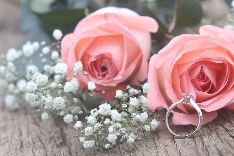 Close-Up Of Pink Roses And Wedding Ring On Table