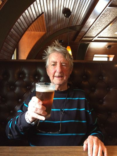 Portrait of senior man with beer glass sitting in bar