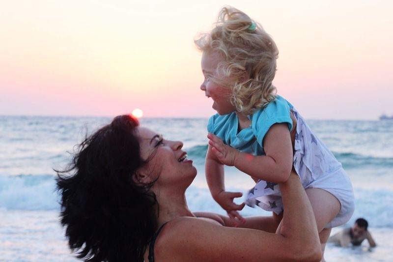 Mother Lifting Cheerful Daughter At Beach Against Sky During Sunset