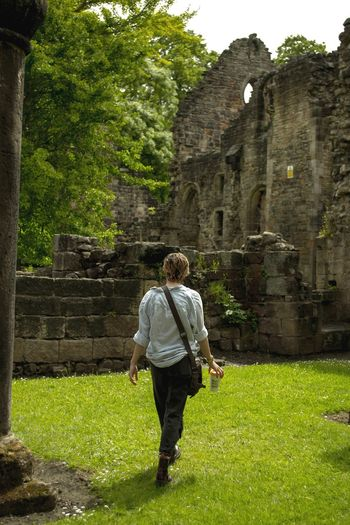 Full length rear view of woman walking on grass against old building