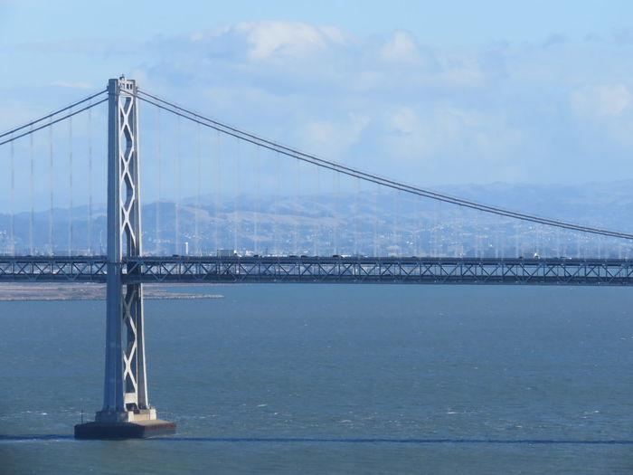 Bay bridge over sea against sky on sunny day