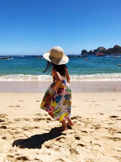 Maddie and the sun Love Happiness Sundress Sunhat Blue Water Blue Sky Sunandsand Sunbathe Daughter Daughtersarethebest Kids Being Kids Beachphotography Beach Day CaboSanLucas Medanobeach Beach Sea Sand Water Hat One Person Rear View Beauty In Nature