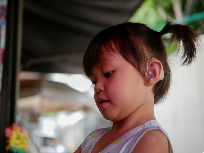 Close-up of cute girl wearing hearing aid