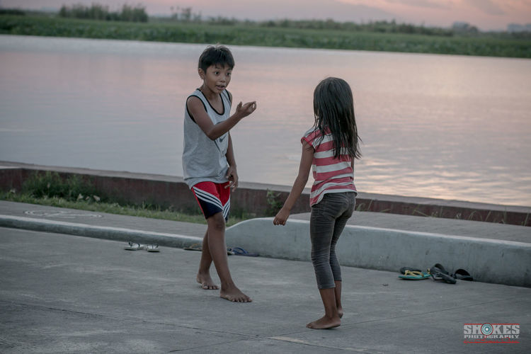 TEASING: A native game of Filipinos called PATINTERO where the player have to pass the guarded line wihout beint touch otherwise the guards will win. In this photo, the girl are the one whose guarding the line while the boy teases her as a part of his plan. #philippines #children #nativegame #filipinos #streetphotographyPH