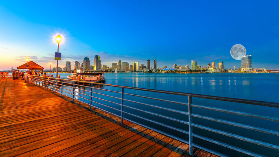 Scenic twiligtht view of Coronado wooden pier with docked ferry boat on Coronado Island, California, USA. San Diego skyline and urban downtown cityscape with big full moon over San Diego Bay. Coronado Coronado Beach Coronado Island Sea Beach San Diego California United States America American Skyline Seascape Cityscape Sun Dock Port Holiday Vacations Sunset Night Moon Pier Built Structure Architecture City Water Building Exterior Sky Travel Destinations Skyscraper Office Building Exterior Urban Skyline Building Tower Illuminated Railing Landscape No People Travel Modern Outdoors