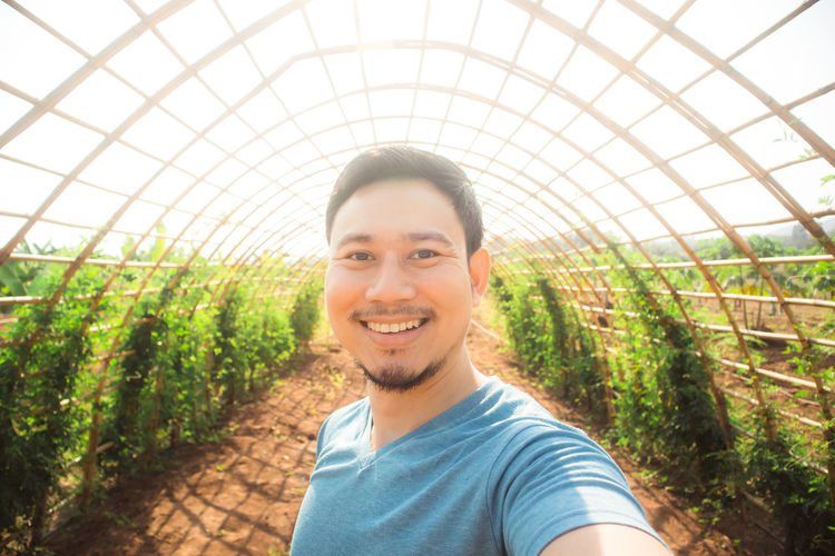 Portrait of smiling young man standing in greenhouse