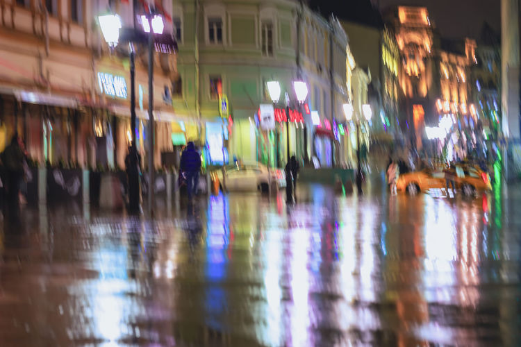 Hurrying young people under umbrellas on a rainy night in street of city. Vivid illumination from lanterns and shop windows. Concept of seasons, weather, modern city. Bright blurred background Illuminated City Night Motion City Rainy Rain Blurred Motion Blur Abstract Evening Street Bright People Reflection Lamps Pavement Umbrella Multi Colored Panoramic Outdoors Light Large Group Of People Women