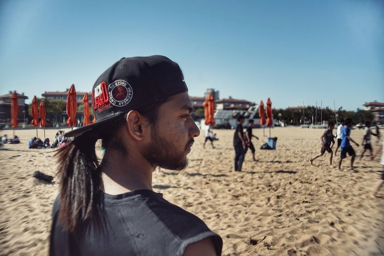 Beach Clear Sky Day Fashion Focus On Foreground Glasses Headshot Incidental People Land Leisure Activity Lifestyles Nature One Person Outdoors Portrait Real People Sand Sky Sunlight Young Adult Young Men