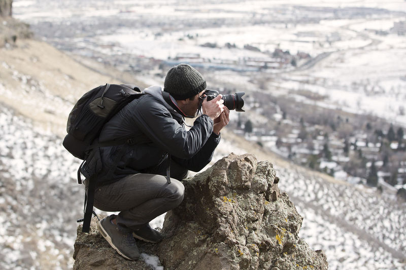 A photographer capturing a beautiful landscape. One Person Real People Rock - Object Rock Photographing Men Photography Themes Camera - Photographic Equipment Activity Day Full Length Technology Holding Land Occupation Clothing Focus On Foreground Photographer Outdoors Skill  Camera Shooting Colorado Message