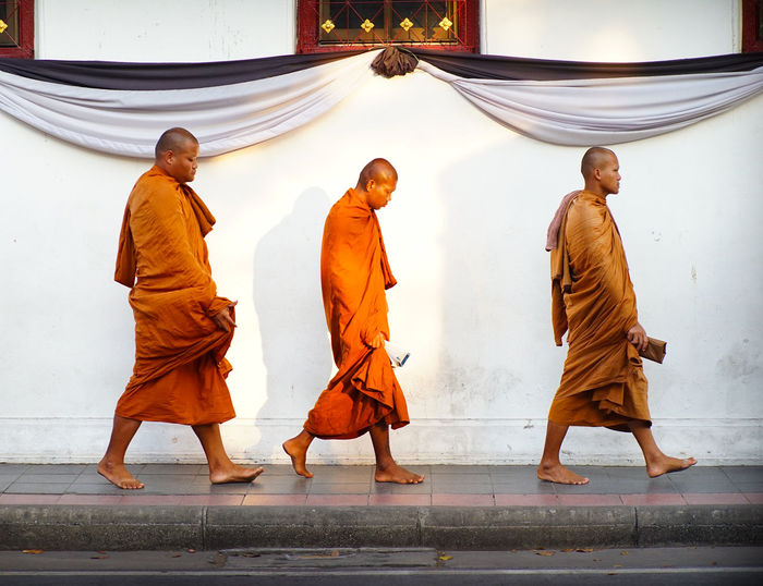 Enlightening path Bangkok Buddhism Buddhist Monks City City Life Monks Orange Outdoors Religion Saffron Robes Spirituality Street Street Photography Temple Wall Walking