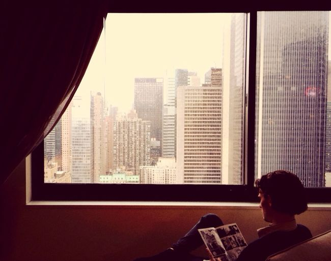 Rear view of man reading magazine by window at home