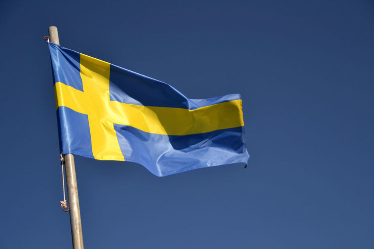 Low angle view of swedish flag against blue sky