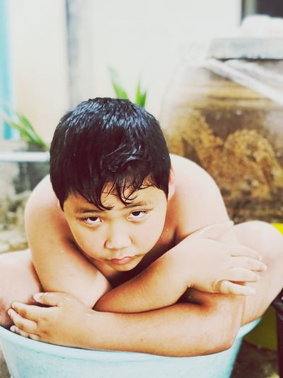 Close-Up Portrait Of Shirtless Boy Sitting In Tub