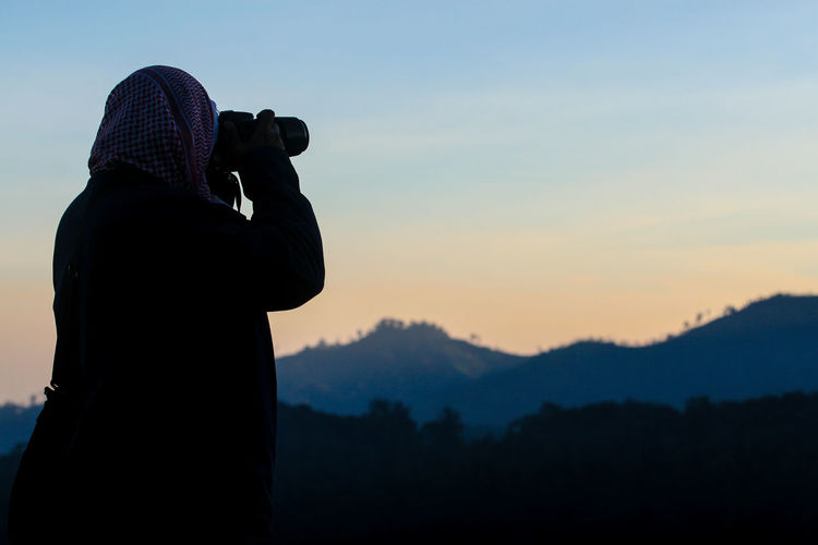 Side View Of A Silhouette Man With Binoculars Against The Sky