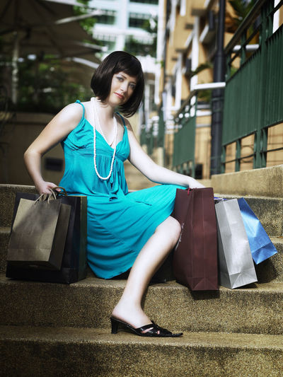 Full Length Of Young Woman Sitting With Shopping Bags On Steps