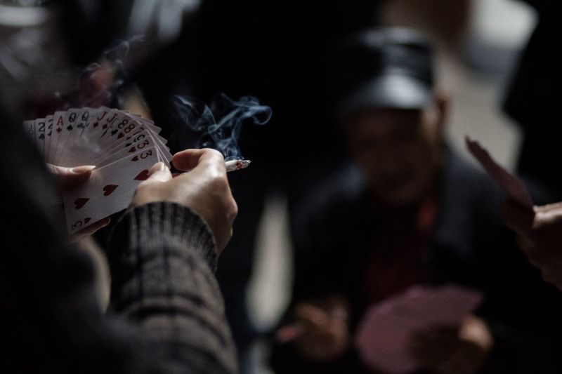 Cropped hands holding cigarette while playing cards