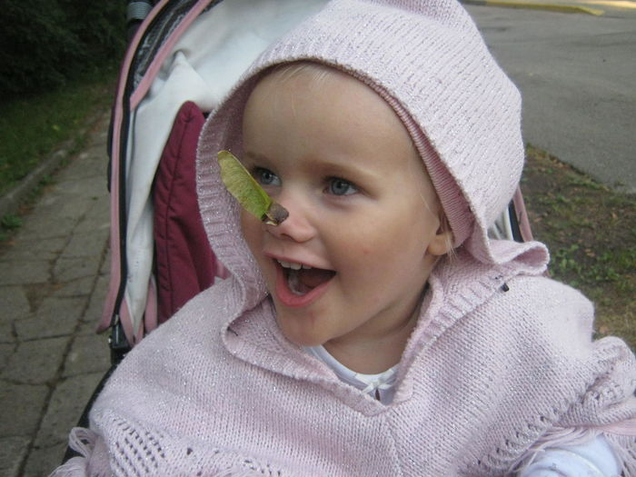 Close-up of thoughtful girl with leaf on nose in baby stroller