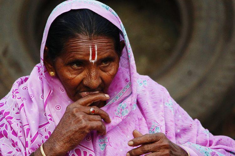 Close-up of senior woman looking away while wearing sari with tilaka